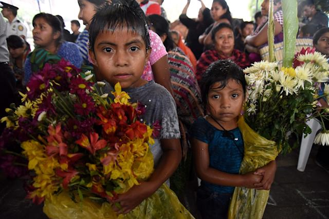 <p>Children hold bunches of flowers during the funeral of 20-year-old Erick Rivas, a victim of the Fuego volcano eruption, in Alotenango municipality, Sacatepequez, about 65 km southwest of Guatemala City, on June 6, 2018 .(Photo: Orlando Estrada/AFP/Getty Images) </p>