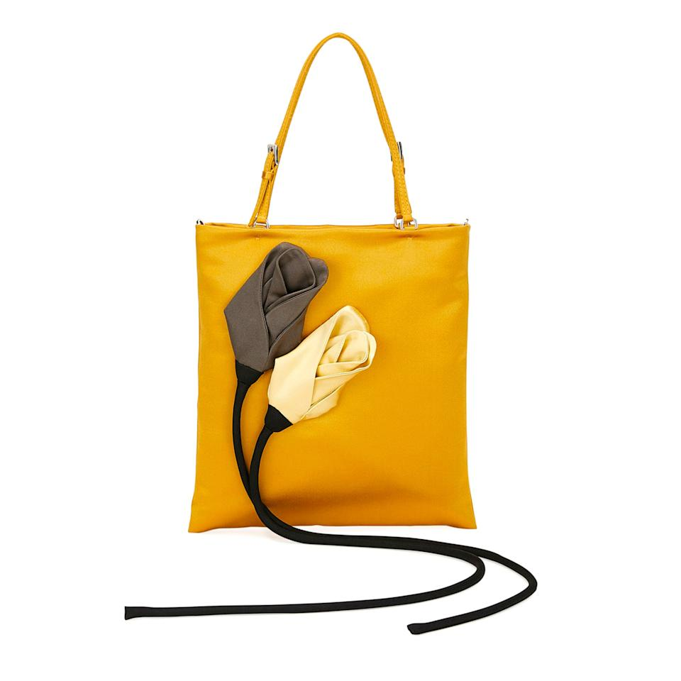 """<p>A bit surreal with dangling flowers, this mustard mini will add interest to any fall look.</p> <p><strong>Buy Now:</strong> Prada, satin flower tote bag, $1,690, <a href=""""https://www.bergdorfgoodman.com/p/prada-satin-flower-tote-bag-prod150570046?parentId=cat268711&icid=&searchType=EndecaDrivenCat&rte=%252Fcategory.jsp%253FitemId%253Dcat268711%2526pageSize%253D30%2526No%253D0%2526refinements%253D&eItemId=prod150570046&cmCat=product"""">bergdorfgoodman.com</a>.</p>"""