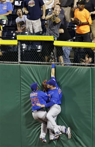 Chicago Cubs right fielder Scott Hairston, right, and Cubs center fielder Julio Borbon (20) collide on the outfield wall as a fan comes up with the catch on a grand slam by Pittsburgh Pirates' Travis Snider during the sixth inning of a baseball game in Pittsburgh on Tuesday, May 21, 2013. (AP Photo/Gene J. Puskar)