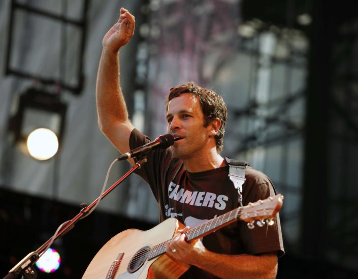"""FILE - This Sept. 22, 2012 file photo shows Jack Johnson performing during the Farm Aid 2012 concert at Hersheypark Stadium in Hershey, Pa. Johnson has agreed to take the Saturday night headlining slot at the Bonnaroo Music & Arts Festival after Mumford & Sons were forced to cancel due to bassist Ted Dwane's illness. Festival officials announced the move Friday morning. The """"Upside Down"""" singer last headlined at Bonnaroo in 2008. (AP Photo/Jacqueline Larma, file)"""