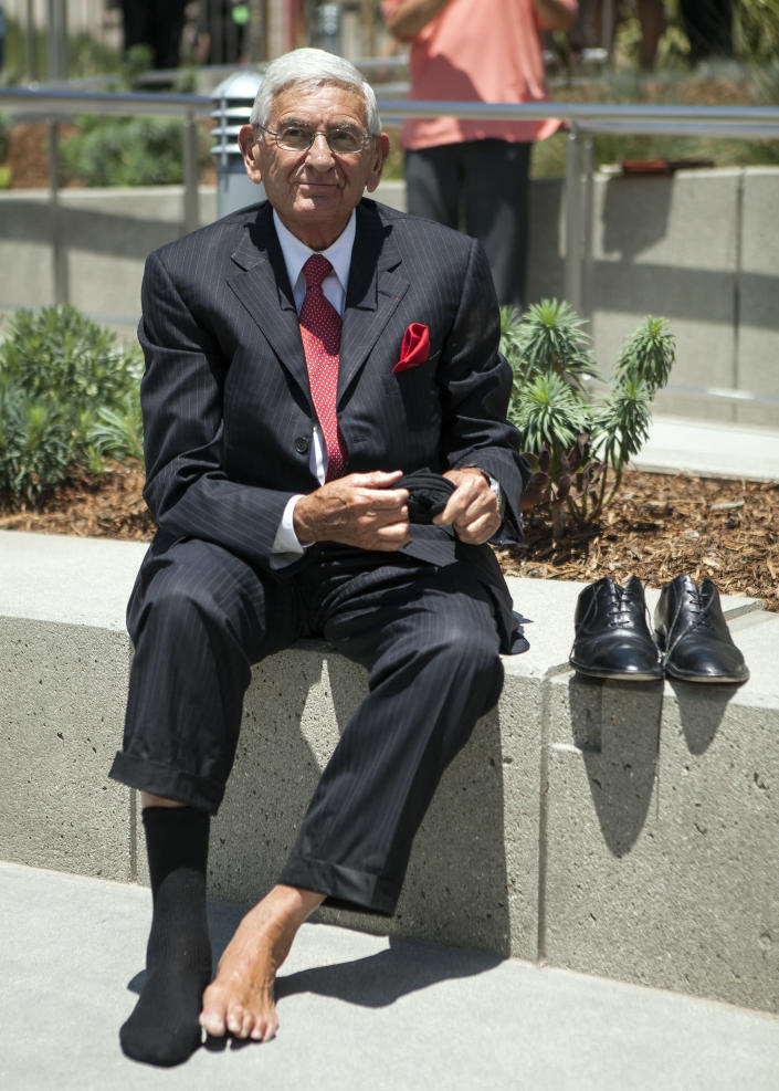 FILE - In this July 26, 2012, file photo, Philantrophist Eli Broad smiles as puts his shoes back on, after an official barefoot walk in the opening of the fountain at Grand Park in Los Angeles. Eli Broad, the billionaire philanthropist, contemporary art collector and entrepreneur who co-founded homebuilding pioneer Kaufman and Broad Inc. and launched financial services giant SunAmerica Inc., died Friday, April 30, 2021 in Los Angeles. He was 87. (AP Photo/Damian Dovarganes, File)