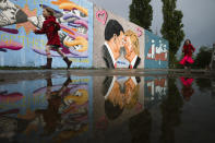 Graffiti depicts U.S. President Trump, right, and China's President Xi Jinping kissing each other with face masks on a wall in the public park Mauerpark in Berlin, Germany, Wednesday, April 29, 2020. (AP Photo/Markus Schreiber)