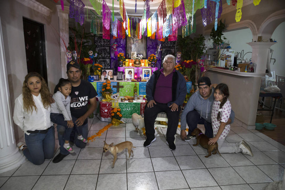 "Salvador Cervantes Torres, center, a recovered COVID-19 patient, and his family pose for photos on a Day of the Dead altar for his wife Ivone Guadalupe Lozano Garcia and his mother in law Silvina Garcia, who died of complications related to coronavirus, at their home in Ecatepec, Mexico, Saturday, Oct. 31, 2020. Mexican families traditionally flock to local cemeteries to honor family members who died as part of the ""Day of the Dead"" holiday, every Nov. 1 and 2, but according to authorities cemeteries will be closed this year to help slow the spread of COVID-19. (AP Photo/Marco Ugarte)"