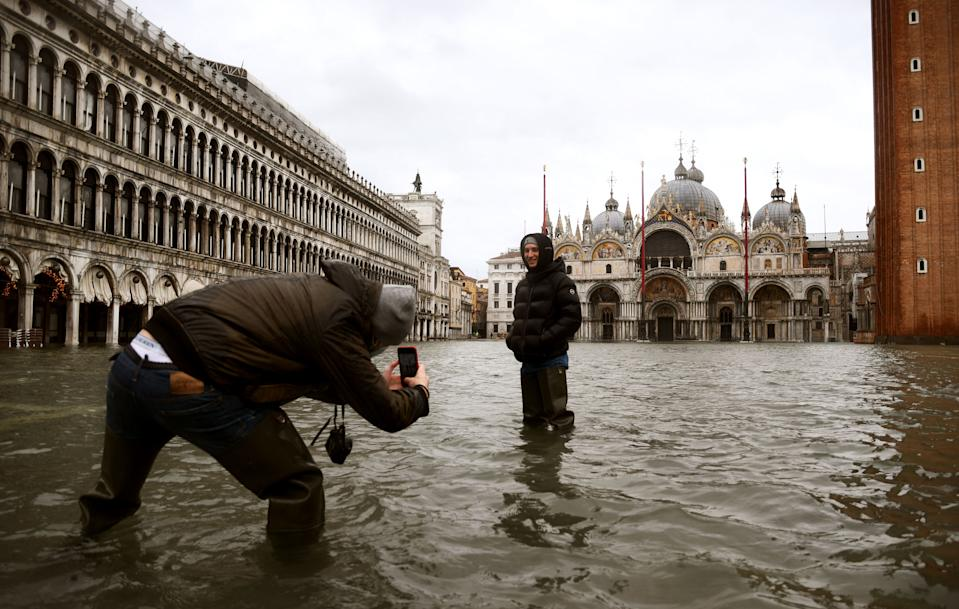 "People talk photos in the middle of a flooded St. Mark's Square on December 8, 2020 in Venice following a high tide ""Alta Acqua"" event following heavy rains and strong winds, and the mobile gates of the MOSE Experimental Electromechanical Module that protects the city of Venice from floods, were not lifted (Photo by ANDREA PATTARO / AFP) (Photo by ANDREA PATTARO/AFP via Getty Images)"