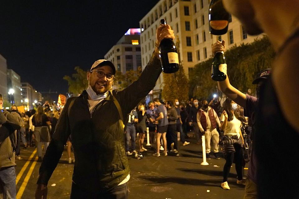 People raise bottles of champagne as they celebrate near the White House.