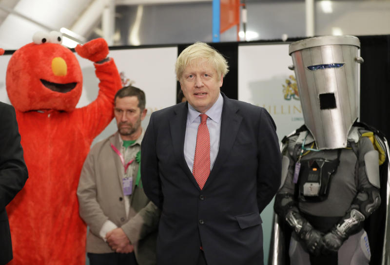 Bobby Smith, a political and fathers' rights activist and founder and leader of the 'Give Me Back Elmo' party, left, and Independent candidate Count Binface stand either side of Britain's Prime Minister and Conservative Party leader Boris Johnson wait for the Uxbridge and South Ruislip constituency count declaration. Source: AP