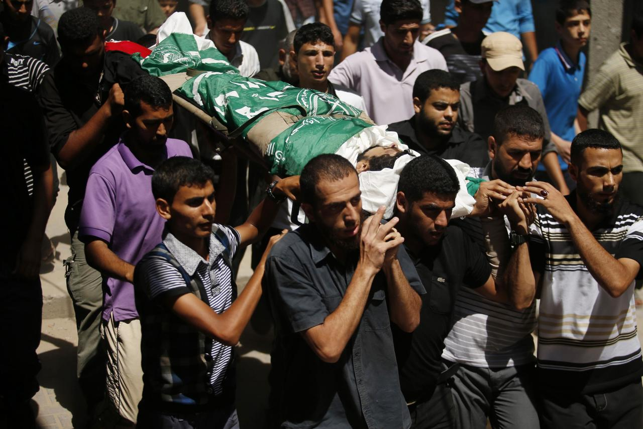 ATTENTION EDITORS - VISUAL COVERAGE OF SCENES OF INJURY OR DEATH  Palestinians carry the body of a Hamas militant, who was killed by an Israeli air strike, during his funeral in Gaza City August 26, 2014. Israeli air strikes launched before dawn on Tuesday killed two Palestinians and destroyed much of one of Gaza's tallest apartment and office buildings, setting off huge explosions and wounding 20 people, Palestinian health officials said. Israel had no immediate comment on the attacks that took place as Egyptian mediators stepped up efforts to achieve an elusive ceasefire to end seven weeks of fighting. Israel launched an offensive on July 8, with the declared aim of ending rocket fire into its territory. REUTERS/Suhaib Salem (GAZA - Tags: POLITICS CIVIL UNREST) TEMPLATE OUT