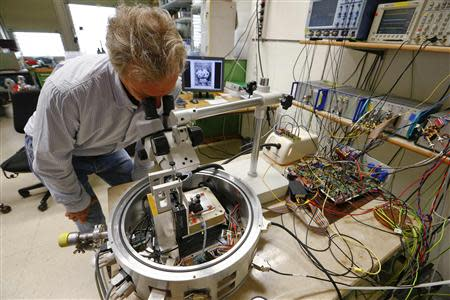 Physicist Urs Duerig looks into a prototype of an IBM NanoFrazor 3D nano printing tool at a laboratory of IBM Research in Rueschlikon, near Zurich, April 23, 2014. REUTERS/Arnd Wiegmann