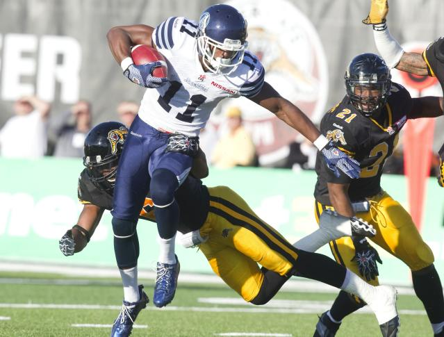 Toronto Argonauts' Dontrelle Inman (C) evades a tackle by Hamilton Tiger-Cats' Nate Bussey in the first half of their CFL football game in Guelph October 14, 2013. REUTERS/Fred Thornhill (CANADA - Tags: SPORT FOOTBALL)