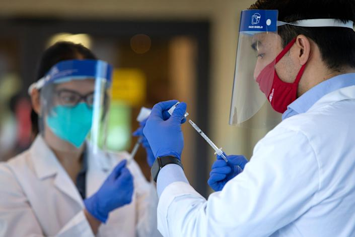 Pharmacists prepare doses of the COVID-19 vaccine at the Life Care Center of Kirkland on Dec. 28, 2020 in Kirkland, Wash. The Life Care Center of Kirkland, a nursing home, was an early epicenter for coronavirus outbreaks in the U.S.