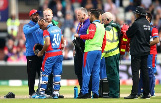 Hashmatullah is assessed by medical staff after being struck by the ball (Tim Goode/PA)