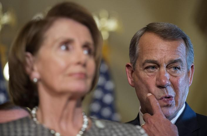 Speaker of the House John Boehner stands behind House Minority Leader Nancy Pelosi during a press conference on Capitol Hill in Washington, DC, September 30, 2014 (AFP Photo/Jim Watson)
