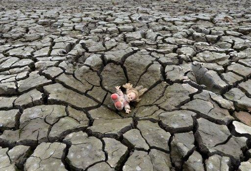 A doll lies on a hole in the dry soil of Los Laureles dam, southern Tegucigalpa, in Honduras on May 22, 2013. The first decade of the 21st century was the hottest on record, marked by unprecedented climate and weather extremes that killed more than 370,000 people, the United Nations weather agency said Wednesday