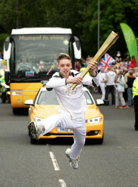 James Hobley carries the Olympic Flame on the Torch Relay leg through Stockton-On-Tees.