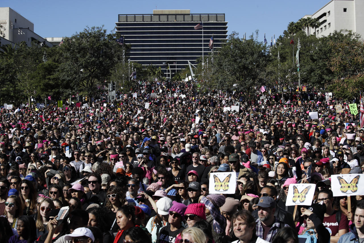 Protesters listen to speeches at the Grand Park during a Women's March, Saturday, Jan. 20, 2018, in Los Angeles. On the anniversary of President Donald Trump's inauguration, people participating in rallies and marches in the U.S. and around the world Saturday denounced his views on immigration, abortion, LGBT rights, women's rights and more. (AP Photo/Jae C. Hong)