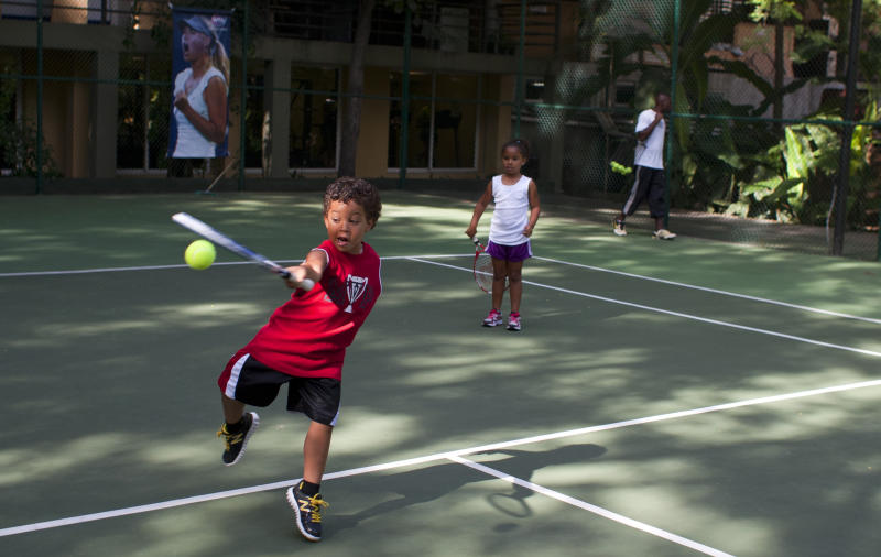 "In this July 3, 2013 photo, Teo Biamby 4, swats a tennis ball as Kaden, his 5-year-old sister watches, while on summer vacation with their parents, at the Karibe Hotel in Port-au-Prince, Haiti. Haiti tourism is a tough sell not just because of its history of political unrest or because it was designated by the U.S. State Department in 2012 as a ""major drug trafficking country."" It's also difficult to sell because its Caribbean neighbors are cheaper; hotels are relatively expensive and fees such as generator fuel and potable water are often included in room rates. (AP Photo/Dieu Nalio Chery)"