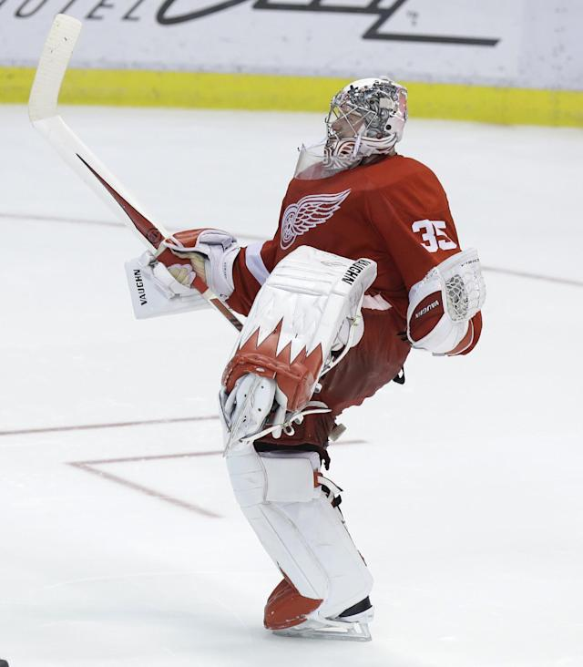 Detroit Red Wings goalie Jimmy Howard (35) celebrates after a 3-2 win after the shootout period of an NHL hockey game against the Los Angeles Kings in Detroit, Saturday, Jan. 18, 2014. (AP Photo/Carlos Osorio)