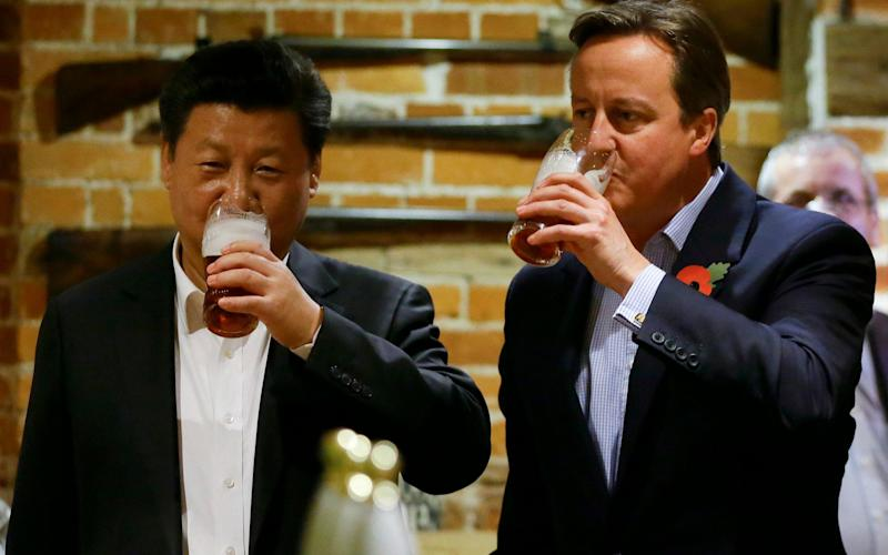 China's President Xi Jinping drinks a pint of beer with David Cameron during his visit to Britain in 2015 - Getty Images