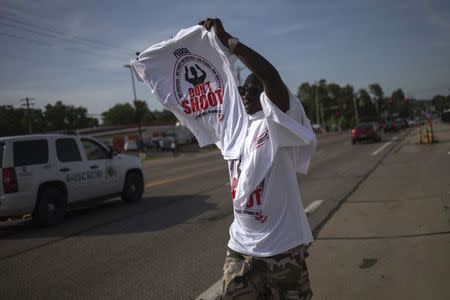 A man sells T-shirts commemorating shooting victim Michael Brown along the roadside in Ferguson, Missouri in this file photo taken August 21, 2014. REUTERS/Adrees Latif/Files