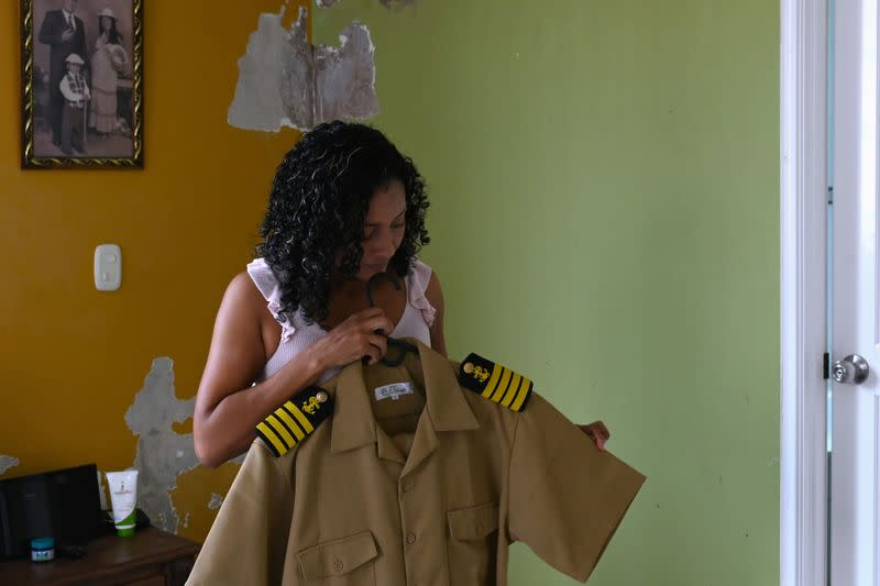 Claudia Patricia Fortich, widow of late oil tanker captain Jaime Herrera Orozco who was murdered on his ship while anchored off Venezuela, holds her deceased husband's uniform suit at her home, in Cartagena