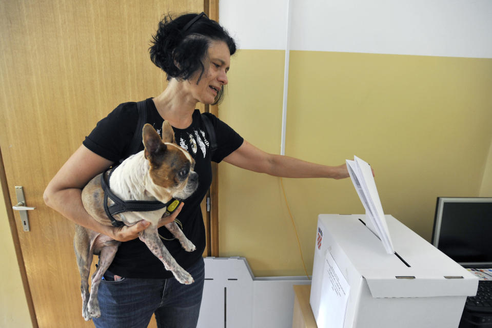 A voter casts her ballot at a polling station in Zagreb, Croatia, Sunday, July 5, 2020. Amid a spike of new coronavirus cases, voters in Croatia cast ballots on Sunday in what is expected be a close parliamentary race that could push the latest European Union member state further to the right. (AP Photo)