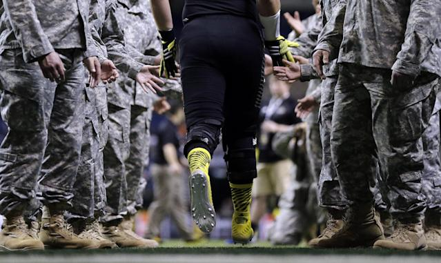 U.S. Army All-American East's Mason Cole, center, is greeted by members of the Army as he runs onto the field for the U.S. Army All-American Bowl football game, Saturday, Jan. 4, 2014, in San Antonio. (AP Photo/Eric Gay)