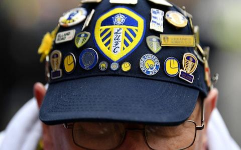 A Leeds fan adorns his cap with badges - Credit: getty images