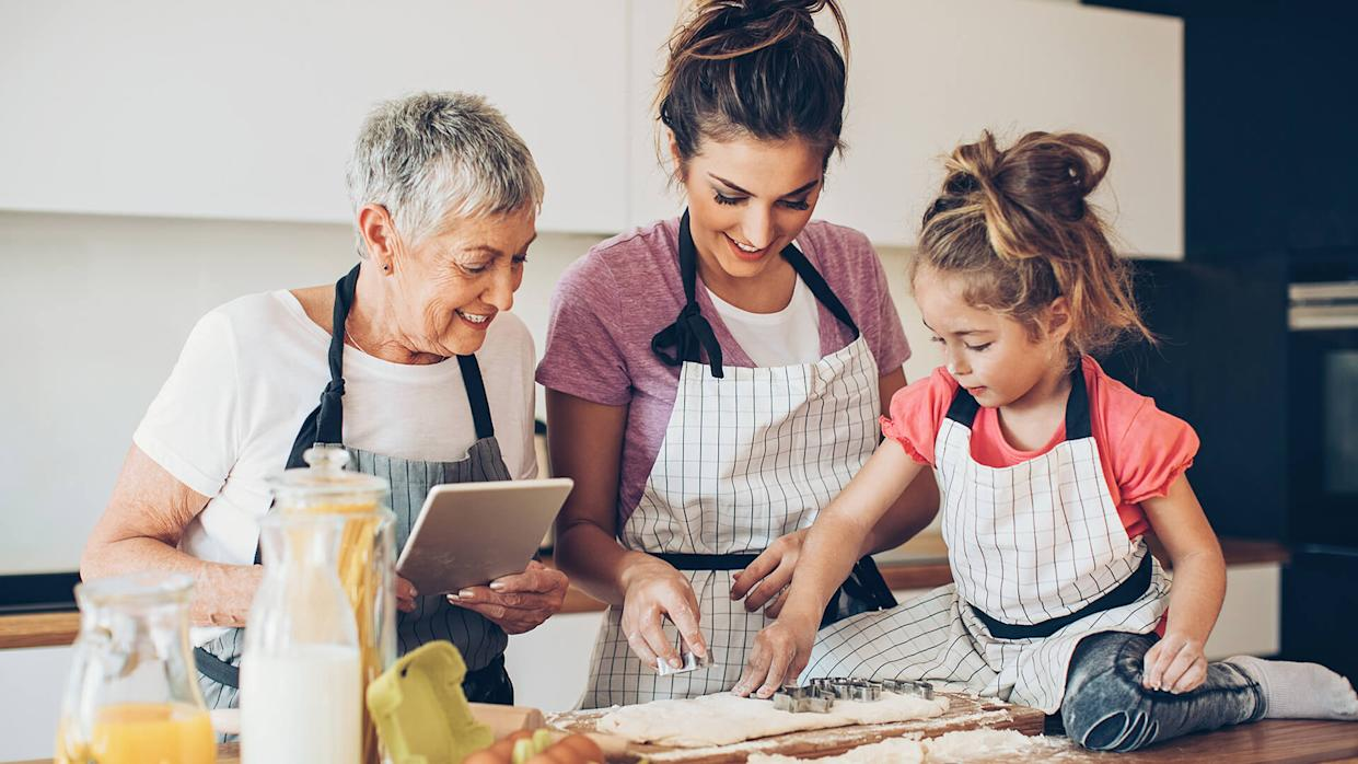 Different generations of women with digital tablet preparing cookies together.