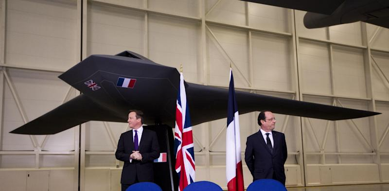 British Prime Minister David Cameron, left, and French President Francois Hollande stand backdropped by a model of a concept design for a future unmanned combat air vehicle as they wait for memorandums of understandings and an agreement to be signed before the start of their press conference at their one-day summit at the RAF Brize Norton air base in Brize Norton, England, Friday, Jan. 31, 2014. The one-day summit covered military cooperation, including talks over armed drones, anti-ship missiles, and underwater mine detectors, as well as a joint Franco-British force of 10,000 soldiers due to be formed in the next few years. (AP Photo/Matt Dunham)