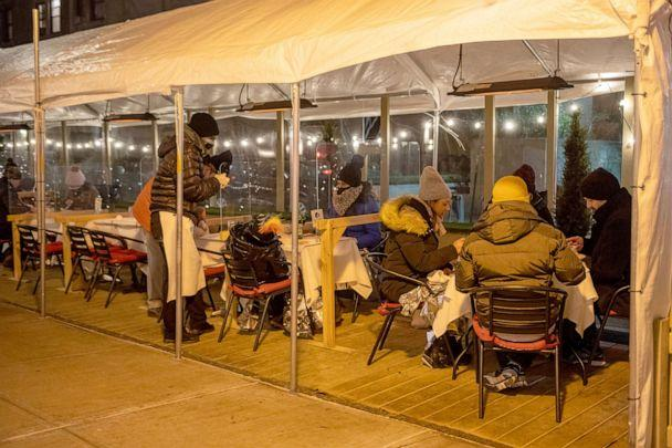 PHOTO: Customers wearing winter jackets sit with emergency thermal blankets while dining outdoors at Cafe Luxembourg as temperatures drop below freezing in New York on Jan. 28, 2021. (Alexi Rosenfeld/Getty Images)