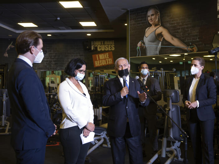 """Israeli Prime Minister Benjamin Netanyahu, center, visits a fitness gym with Austrian Chancellor Sebastian Kurz, left, and Danish Prime Minister Mette Frederiksen, right, to observe how the """"Green Pass,"""" for citizens vaccinated against COVID-19, is used, in Modi'in, Israel, Thursday, March 4, 2021. Frederiksen and Kurz are on a short visit to Israel for to pursue the possibilities for closer cooperation on COVID-19 and vaccines. (Avigail Uzi/Pool via AP)"""