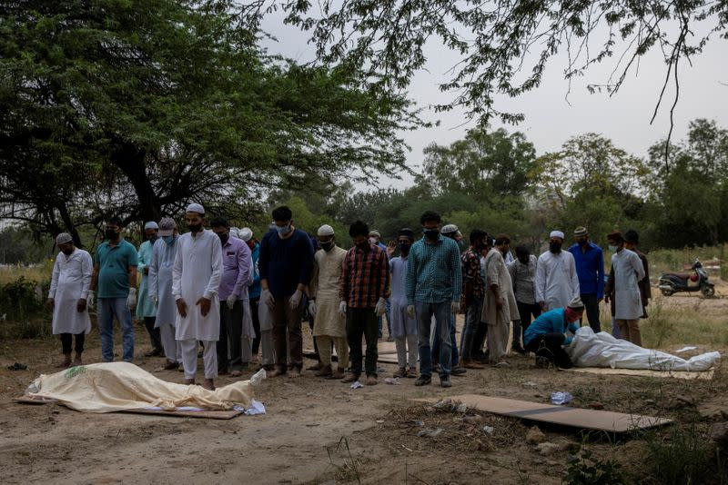 People bury the bodies of COVID-19 victims in New Delhi