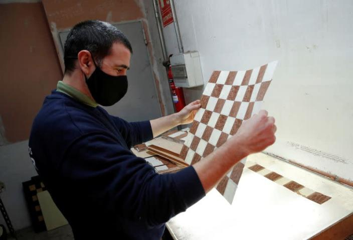 A worker makes a chessboard at the Rechapados Ferrer factory at their factory in La Garriga