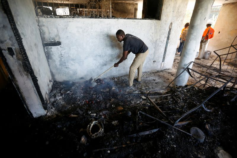 A man removes burning debris inside a bedroom at an orphanage after it was destroyed in a fire, in Port-au-Prince