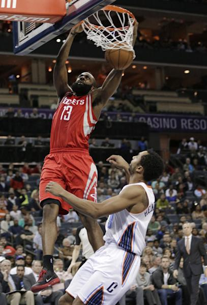 Houston Rockets' James Harden (13) dunks above Charlotte Bobcats' Gerald Henderson (9) during the second half of an NBA basketball game in Charlotte, N.C., Monday, Jan. 21, 2013. Houston won 100-94. (AP Photo/Chuck Burton)
