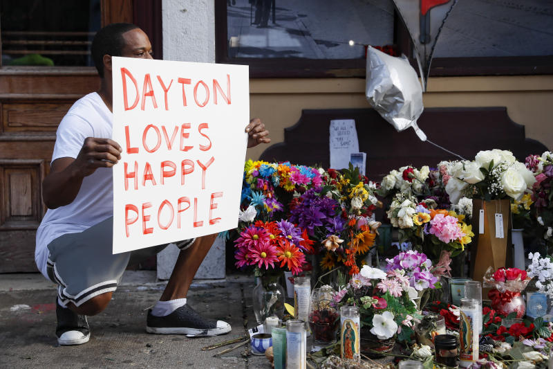 Damon Smith presents what he describes as a positive message before the arrival of President Donald Trump near a makeshift memorial for the slain and injured victims of a mass shooting that occurred in the Oregon District early Sunday morning, Aug. 7, 2019, in Dayton, Ohio. President Donald Trump headed to Dayton and El Paso, Texas on Wednesday to offer a message of healing and unity, but he will be met by unusual hostility in both places by people who fault his own incendiary words as a contributing cause to the mass shootings. (Photo: John Minchillo/AP)