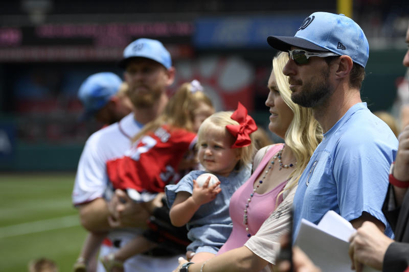 Washington Nationals' Max Scherzer and his wife Erica, second from right, holding their daughter Brooklyn, stand on the field before a baseball game against the Arizona Diamondbacks, Sunday, June 16, 2019, in Washington. (AP Photo/Nick Wass)