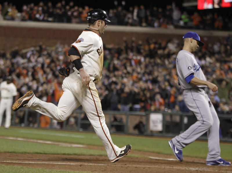 San Francisco Giants' Aaron Rowand, left, runs in to score the Giants' fifth run on a wild pitch as Los Angeles Dodgers relief pitcher Blake Hawksworth, right, covers home plate during the seventh inning of their baseball game in San Francisco, Tuesday, April, 12, 2011. (AP Photo/Eric Risberg)
