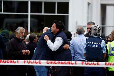 People embrace as they gather for prayers following Friday's shooting outside the Linwood Mosque in Christchurch New Zealand