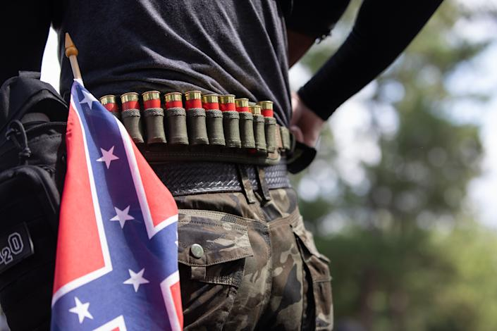 A man with ammunition can be seen in front of a confederate flag as members of far right militias and white pride organizations rally near Stone Mountain Park in downtown Stone Mountain, Georgia on August 15, 2020. - Militia members, such as III%, clashed with anti-racist and anti-fascist protesters organized by F.L.O.W.E.R, a frontline organization based in Atlanta to combat racism. (Logan Cyrus/AFP via Getty Images)