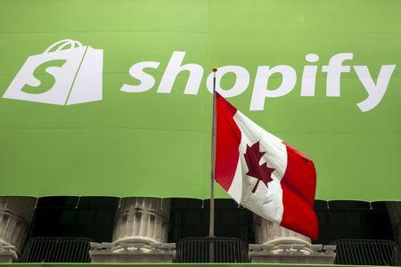 The logo of Shopify hangs behind the Canadian flag after the company's IPO at the New York Stock Exchange