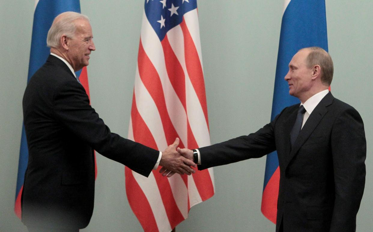 Russian Prime Minister Vladimir Putin (R) shakes hands with then U.S. Vice President Joe Biden during their meeting in Moscow March 10, 2011. (Alexander Natruskin/Reuters)