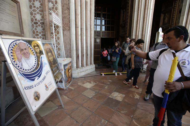 Tourists and pilgrims take pictures of a poster announcing Pope Francis' visit outside the St. Francis Basilica, in Assisi, Italy, Thursday, Oct. 3, 2013. The pontiff is scheduled to visit Assisi, the birthplace of the Italian saint who inspired his name on Friday. (AP Photo/Gregorio Borgia)