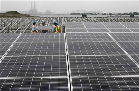 Workers set up a solar panel at a solar power field in Kawasaki, near Tokyo in this June 27, 2011 file photo. REUTERS/Toru Hanai/Files