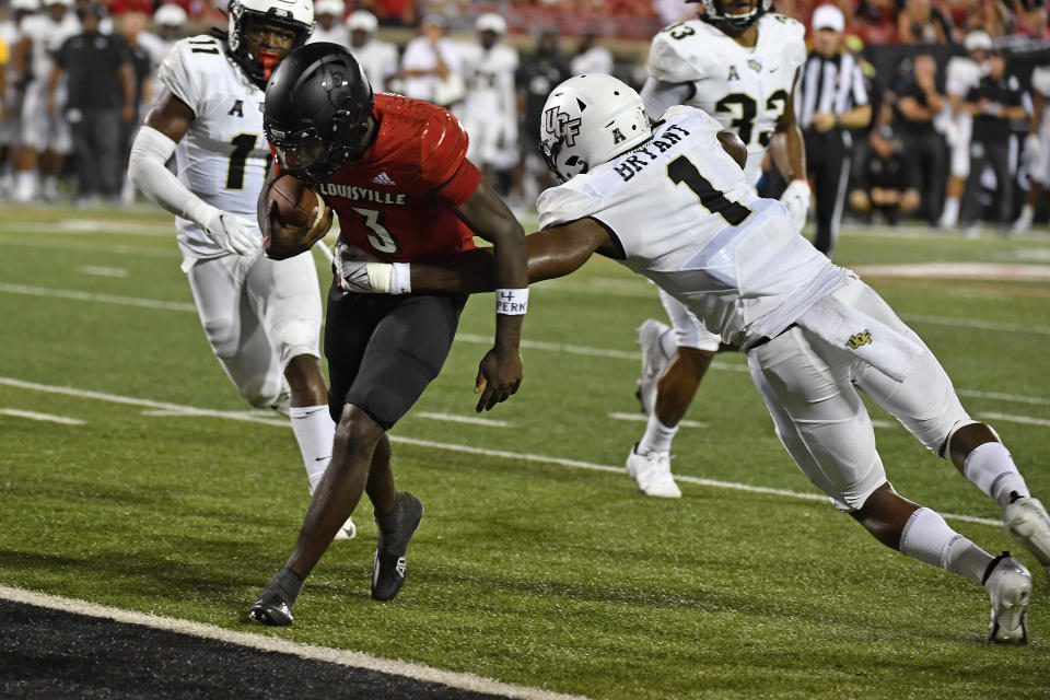 Central Florida defensive lineman Big Kat Bryant (1) attempts to tackle Louisville quarterback Malik Cunningham (3) who scores a touchdown during the second half of an NCAA college football game in Louisville, Ky., Friday, Sept. 17, 2021. (AP Photo/Timothy D. Easley)