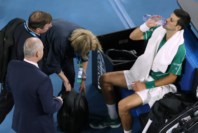 Serbia's Novak Djokovic is attended to by medical staff during his men's singles final against Austria's Dominic Thiem at the Australian Open tennis championship in Melbourne, Australia, Sunday, Feb. 2, 2020. (AP Photo/Andy Wong)