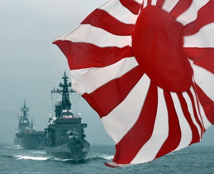 The flag of the Japanese Maritime Self-Defense Force flutters in the wind during a fleet review on October 14, 2012. Japan will increase military spending in 2013 for the first time in more than a decade, the ruling party said