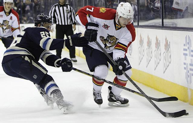 Florida Panthers' Dmitry Kulikov, right, tries to pass the puck past Columbus Blue Jackets' Corey Tropp during the third period of an NHL hockey game on Saturday, Feb. 1, 2014, in Columbus, Ohio. The Blue Jackets won 4-1. (AP Photo/Jay LaPrete)