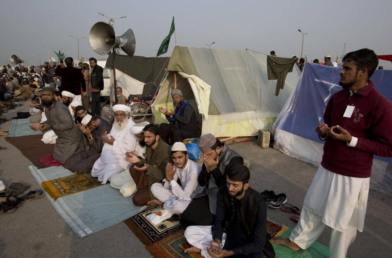 Protesters offer prayers sit outside their make-shift tents during a sit-in protest at an entrance of Islamabad, Pakistan, Friday, Nov. 17, 2017. Pakistani police have warned an Islamist rally to disband within hours to avoid a crackdown near the capital, where an estimated 5,000 members of a radical Islamic party have camped out and disrupted life. (AP Photo/B.K. Bangash)