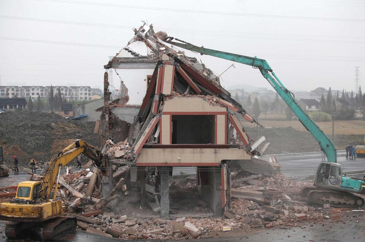 The house is finally demolished, despite the road already built around it (Rex)